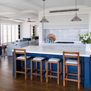 Inspiration for a transitional galley open plan kitchen in Brisbane with marble benchtops, subway tile splashback, stainless steel appliances, with island, beaded inset cabinets, blue cabinets, white splashback, dark hardwood floors, brown floor and white benchtop.