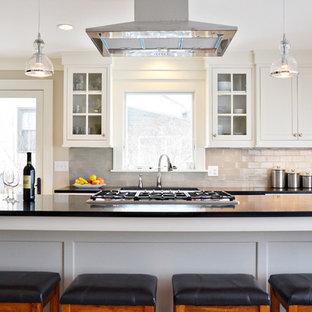 Inspiration för ett mellanstort funkis linjärt kök med öppen planlösning, med en rustik diskho, vita skåp, grått stänkskydd, stänkskydd i tunnelbanekakel, rostfria vitvaror, ljust trägolv, en köksö, bänkskiva i täljsten och skåp i shakerstil
