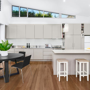 Photo of a mid-sized contemporary galley eat-in kitchen in Sydney with a double-bowl sink, grey cabinets, quartz benchtops, white splashback, glass sheet splashback, stainless steel appliances, medium hardwood floors, with island, white benchtop, flat-panel cabinets and brown floor.