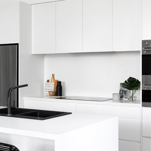 Design ideas for a contemporary galley kitchen in Melbourne with a drop-in sink, flat-panel cabinets, white cabinets, stainless steel appliances, medium hardwood floors, with island, brown floor and white benchtop.