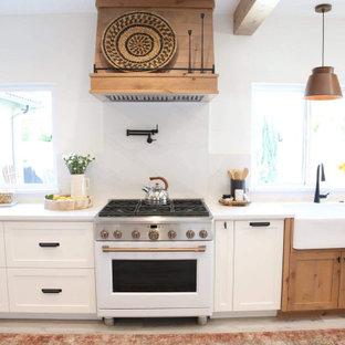 Immagine di una grande cucina minimalista con lavello stile country, ante in stile shaker, ante bianche, top in quarzo composito, paraspruzzi bianco, paraspruzzi in quarzo composito, elettrodomestici bianchi, pavimento in laminato, isola, pavimento grigio, top bianco e travi a vista