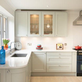 Design ideas for a medium sized traditional l-shaped kitchen in Berkshire with a submerged sink, shaker cabinets, green cabinets, coloured appliances, beige floors and white worktops.
