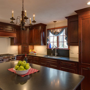 Traditional eat-in kitchen designs - Elegant l-shaped medium tone wood floor eat-in kitchen photo in Boston with a drop-in sink, raised-panel cabinets, dark wood cabinets, solid surface countertops and an island