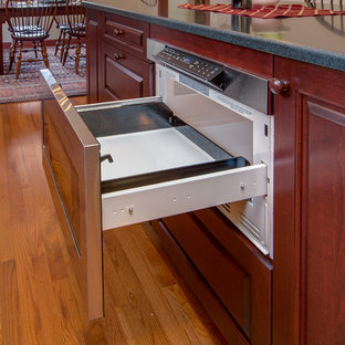 Traditional eat-in kitchen ideas - Example of a classic l-shaped medium tone wood floor eat-in kitchen design in Boston with a drop-in sink, raised-panel cabinets, dark wood cabinets, solid surface countertops and an island