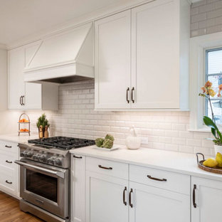 Example of a mid-sized transitional u-shaped medium tone wood floor and brown floor eat-in kitchen design in Indianapolis with a farmhouse sink, shaker cabinets, white cabinets, quartz countertops, white backsplash, ceramic backsplash, stainless steel appliances, an island and white countertops