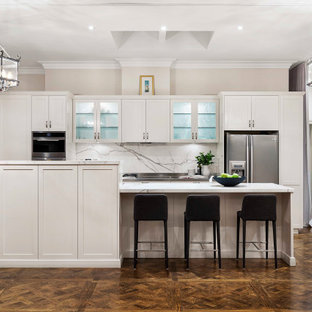 This is an example of a large transitional galley open plan kitchen in Melbourne with shaker cabinets, white cabinets, marble benchtops, white splashback, marble splashback, stainless steel appliances, with island, brown floor, white benchtop and dark hardwood floors.