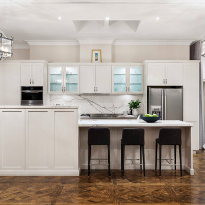 Inspiration for a large transitional galley brown floor and dark wood floor open concept kitchen remodel in Melbourne with shaker cabinets, white cabinets, marble countertops, white backsplash, marble backsplash, stainless steel appliances, an island and white countertops
