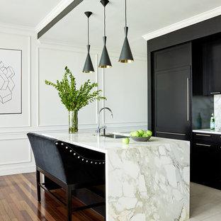 Immagine di una cucina minimal con lavello sottopiano, ante lisce, ante nere, elettrodomestici da incasso e isola