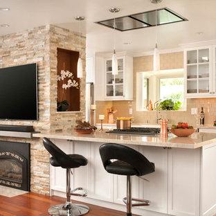 Idée de décoration pour une cuisine ouverte tradition avec un placard à porte vitrée, des portes de placard blanches, une crédence beige, une crédence en carrelage métro, un sol en bois brun, une péninsule, un sol orange et un plan de travail beige.