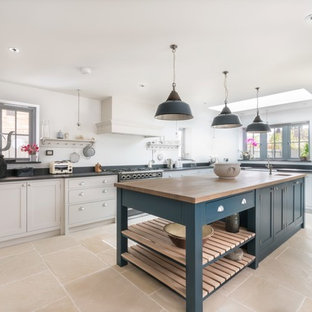 Design ideas for an expansive traditional u-shaped kitchen in Essex with a belfast sink, shaker cabinets, grey cabinets, granite worktops, white splashback, terracotta flooring, an island, beige floors, black worktops and stainless steel appliances.
