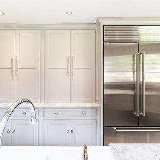 Inredning av ett avskilt, stort grå grått parallellkök, med en rustik diskho, skåp i shakerstil, grå skåp, bänkskiva i kvartsit, stänkskydd med metallisk yta, glaspanel som stänkskydd, rostfria vitvaror och en köksö