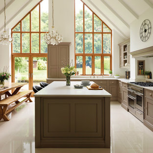 Medium sized farmhouse kitchen/diner in Manchester with shaker cabinets, an island, brown cabinets and stainless steel appliances.
