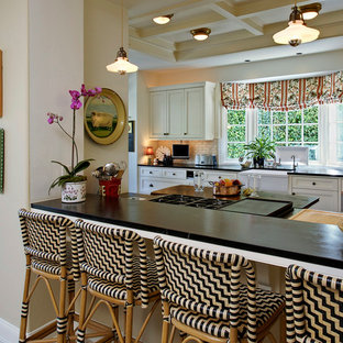 Mid-sized traditional galley eat-in kitchen in Orange County with a farmhouse sink, recessed-panel cabinets, white cabinets, soapstone benchtops, white splashback, ceramic splashback, stainless steel appliances, marble floors and no island.
