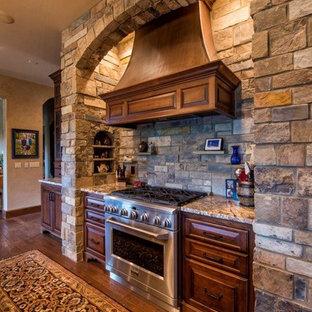 Offene, Große Klassische Küche in L-Form mit profilierten Schrankfronten, Unterbauwaschbecken, dunklen Holzschränken, Granit-Arbeitsplatte, Küchengeräten aus Edelstahl, dunklem Holzboden und Kücheninsel in Sonstige