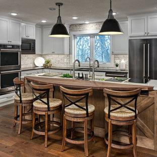 ミネアポリスの中くらいのトランジショナルスタイルのおしゃれなキッチン (アンダーカウンターシンク、シェーカースタイル扉のキャビネット、グレーのキャビネット、白いキッチンパネル、レンガのキッチンパネル、シルバーの調理設備、濃色無垢フローリング、茶色い床、マルチカラーのキッチンカウンター) の写真