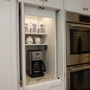 Photo of a large traditional kitchen pantry in Cleveland with a submerged sink, white cabinets, quartz worktops, white splashback, porcelain splashback, stainless steel appliances, dark hardwood flooring, an island, brown floors, white worktops and shaker cabinets.