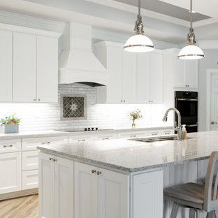 Inspiration for an expansive transitional l-shaped eat-in kitchen in Charlotte with a triple-bowl sink, shaker cabinets, white cabinets, quartz benchtops, white splashback, marble splashback, stainless steel appliances, light hardwood floors, with island, grey floor and multi-coloured benchtop.