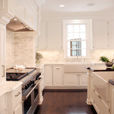 Elegant kitchen photo in Cleveland with stainless steel appliances, a farmhouse sink, white backsplash, raised-panel cabinets, white cabinets and marble backsplash