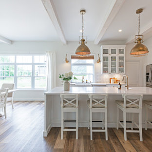 Design ideas for a traditional galley eat-in kitchen in New York with a drop-in sink, open cabinets, white cabinets, quartzite benchtops, white splashback, ceramic splashback, stainless steel appliances, dark hardwood floors, with island and white benchtop.
