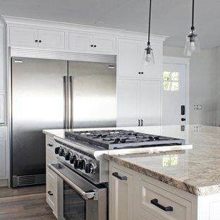 ニューヨークの広いビーチスタイルのおしゃれなキッチン (アンダーカウンターシンク、フラットパネル扉のキャビネット、白いキャビネット、御影石カウンター、シルバーの調理設備、クッションフロア、グレーの床) の写真