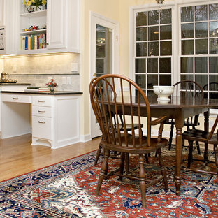 Large traditional eat-in kitchen ideas - Inspiration for a large timeless l-shaped eat-in kitchen remodel in Raleigh with an undermount sink, raised-panel cabinets, white cabinets, granite countertops, white backsplash, subway tile backsplash, white appliances and two islands
