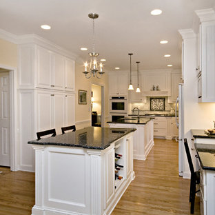 Large traditional eat-in kitchen ideas - Example of a large classic l-shaped eat-in kitchen design in Raleigh with an undermount sink, raised-panel cabinets, white cabinets, granite countertops, white backsplash, subway tile backsplash, white appliances and two islands