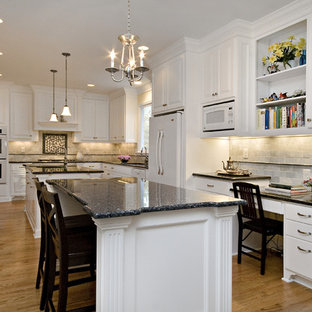 Photo of a large classic l-shaped kitchen/diner in Raleigh with white appliances, a submerged sink, raised-panel cabinets, white cabinets, granite worktops, white splashback, blue worktops, marble splashback, medium hardwood flooring, multiple islands and orange floors.