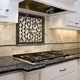 This is an example of a large traditional l-shaped eat-in kitchen in Raleigh with an undermount sink, raised-panel cabinets, white cabinets, granite benchtops, white splashback, subway tile splashback, white appliances and multiple islands.