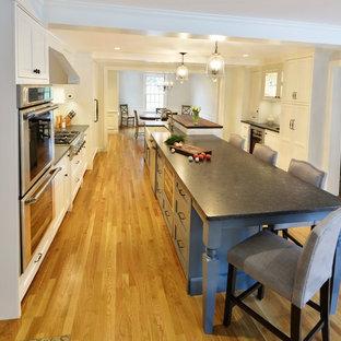 ボストンの広いトラディショナルスタイルのおしゃれなキッチン (エプロンフロントシンク、フラットパネル扉のキャビネット、白いキャビネット、御影石カウンター、白いキッチンパネル、セラミックタイルのキッチンパネル、シルバーの調理設備、淡色無垢フローリング) の写真