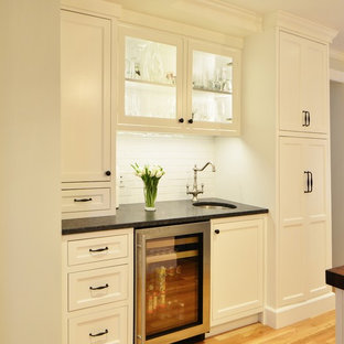 Design ideas for a large traditional kitchen/diner in Boston with a belfast sink, flat-panel cabinets, white cabinets, granite worktops, white splashback, ceramic splashback, stainless steel appliances, light hardwood flooring and an island.