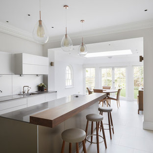 Inspiration for a large contemporary u-shaped kitchen/diner in London with flat-panel cabinets, white cabinets, granite worktops, integrated appliances, ceramic flooring, a breakfast bar and white floors.