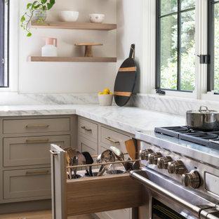 ニューヨークの広いトランジショナルスタイルのおしゃれなキッチン (アンダーカウンターシンク、シェーカースタイル扉のキャビネット、淡色木目調キャビネット、大理石カウンター、白いキッチンパネル、大理石のキッチンパネル、シルバーの調理設備、淡色無垢フローリング、ベージュの床、白いキッチンカウンター) の写真