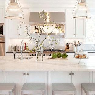 Klassische Küche mit Küchengeräten aus Edelstahl, Marmor-Arbeitsplatte, Schrankfronten mit vertiefter Füllung, weißen Schränken, Küchenrückwand in Weiß, Rückwand aus Metrofliesen und weißer Arbeitsplatte in New York