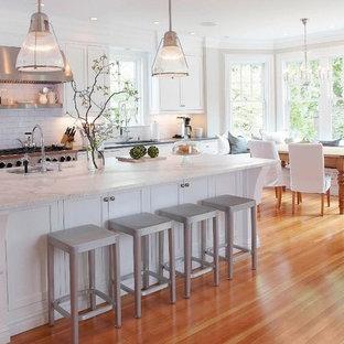 ニューヨークのトラディショナルスタイルのおしゃれなダイニングキッチン (サブウェイタイルのキッチンパネル、大理石カウンター、落し込みパネル扉のキャビネット、白いキャビネット、白いキッチンパネル、白いキッチンカウンター) の写真