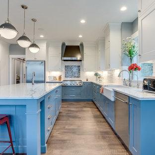 Foto på ett mycket stort maritimt grå u-kök, med en rustik diskho, skåp i shakerstil, blå skåp, vitt stänkskydd, rostfria vitvaror, en köksö och beiget golv