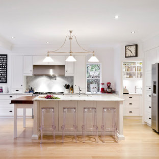 This is an example of a transitional l-shaped eat-in kitchen in Brisbane with shaker cabinets, white cabinets, grey splashback, stainless steel appliances, light hardwood floors, with island, beige floor and grey benchtop.