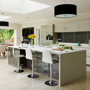 Inspiration for a large contemporary u-shaped open plan kitchen in Essex with an undermount sink, flat-panel cabinets, beige cabinets, grey splashback, stainless steel appliances, ceramic floors, a peninsula and beige floor.