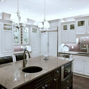 他の地域の広いヴィクトリアン調のおしゃれなキッチン (ドロップインシンク、白いキャビネット、御影石カウンター、茶色いキッチンパネル、シルバーの調理設備、無垢フローリング) の写真