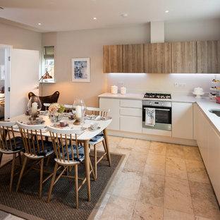 Modelo de cocina comedor en L, actual, de tamaño medio, sin isla, con fregadero de un seno, armarios con paneles lisos, salpicadero blanco, suelo de piedra caliza y suelo beige