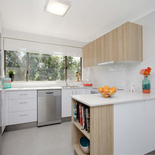 Medium sized contemporary u-shaped kitchen/diner in Brisbane with a double-bowl sink, white cabinets, glass worktops, white splashback, ceramic splashback, stainless steel appliances, porcelain flooring and an island.