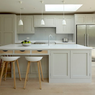 Inspiration for a mid-sized transitional single-wall open plan kitchen in Surrey with an integrated sink, shaker cabinets, grey cabinets, quartz benchtops, white splashback, glass sheet splashback, stainless steel appliances, light hardwood floors, with island and beige floor.