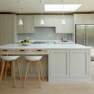 Idéer för att renovera ett mellanstort vintage linjärt kök med öppen planlösning, med en integrerad diskho, skåp i shakerstil, grå skåp, bänkskiva i kvarts, vitt stänkskydd, glaspanel som stänkskydd, rostfria vitvaror, ljust trägolv, en köksö och beiget golv