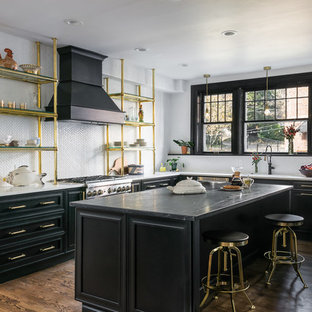 Large traditional kitchen inspiration - Example of a large classic l-shaped brown floor and dark wood floor kitchen design in St Louis with black cabinets, soapstone countertops, white backsplash, ceramic backsplash, stainless steel appliances, an island, gray countertops and recessed-panel cabinets