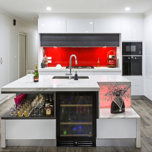 Mid-sized contemporary kitchen pantry ideas - Example of a mid-sized trendy l-shaped laminate floor and gray floor kitchen pantry design in Melbourne with an undermount sink, flat-panel cabinets, white cabinets, quartz countertops, red backsplash, glass sheet backsplash, stainless steel appliances and an island