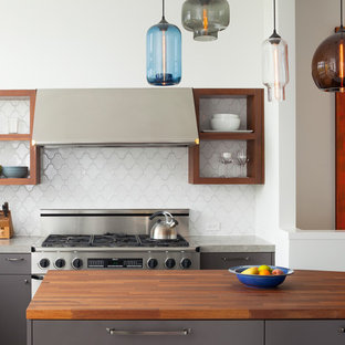 Contemporary kitchen pictures - Example of a trendy kitchen design in San Francisco with flat-panel cabinets, wood countertops, white backsplash, stainless steel appliances and gray cabinets