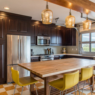 Mid-sized transitional l-shaped open plan kitchen in Portland with dark wood cabinets, glass tile splashback, stainless steel appliances, with island, an undermount sink, raised-panel cabinets, quartz benchtops, green splashback, linoleum floors and multi-coloured floor.