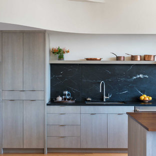Mid-sized eclectic single-wall open plan kitchen in Boston with an undermount sink, flat-panel cabinets, light wood cabinets, soapstone benchtops, black splashback, stone slab splashback, panelled appliances, light hardwood floors and with island.