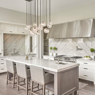 Inspiration for a transitional l-shaped dark wood floor and gray floor kitchen remodel in Chicago with a single-bowl sink, white cabinets, quartzite countertops, stainless steel appliances, shaker cabinets, white backsplash, an island, stone slab backsplash and gray countertops