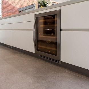 Große Moderne Küche in L-Form mit Triple-Waschtisch, flächenbündigen Schrankfronten, weißen Schränken, Küchenrückwand in Grau, Rückwand aus Steinfliesen, schwarzen Elektrogeräten, Keramikboden, Kücheninsel und grauem Boden in Hampshire