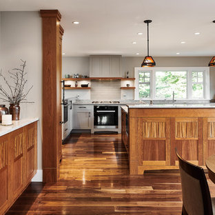 This is an example of a large transitional u-shaped eat-in kitchen in Vancouver with shaker cabinets, medium wood cabinets, quartzite benchtops, multi-coloured splashback, slate splashback, stainless steel appliances, medium hardwood floors, with island and multi-coloured floor.